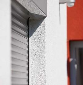 Alulux Aluminium Rollladen auf weiß-roter Hausfassade in Nahaufnahme