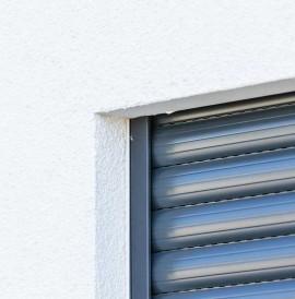 Aufsatzrollladen an weißer Hausfassade in der Nahaufnahme